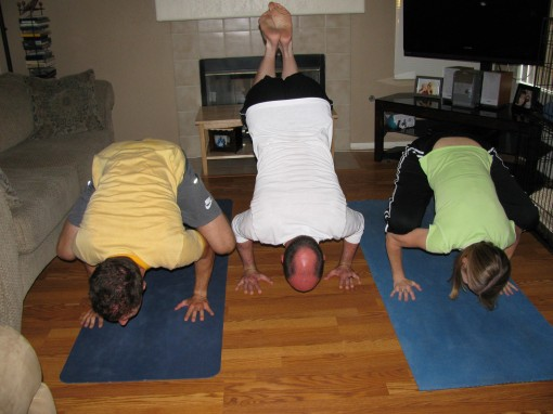 "This is ""Crow Pose"". You can't really tell, but our heads and feet are off the ground. We're just balancing on our hands. For some reason, I can do this pose with relative ease. Needless to say, all present (including me) were impressed."